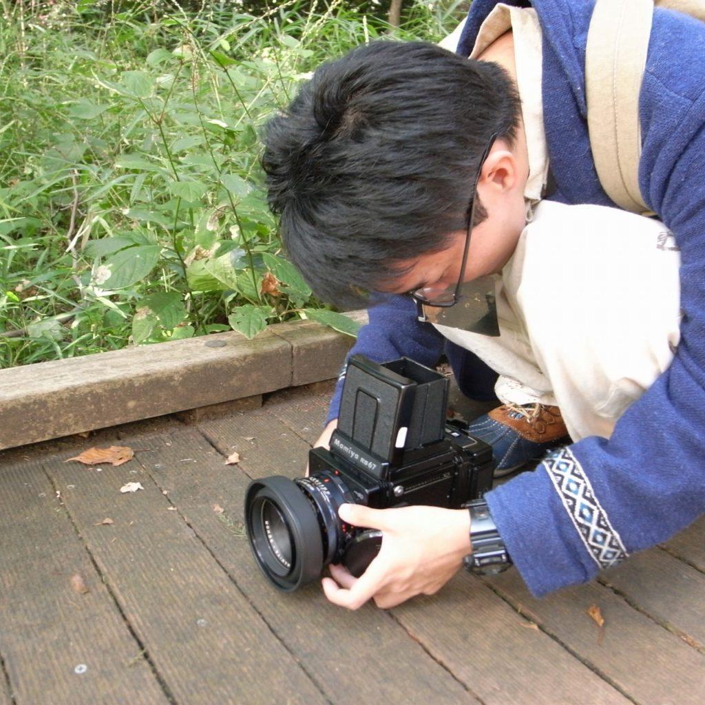 中判カメラを使って撮影する男子学生